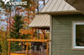 wooden balcony with chairs attached to home in forest during the fall