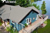 aerial view of cottage on lake with balcony and new roof