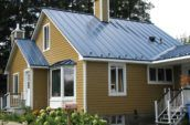 exterior of small yellow home with new metal roof