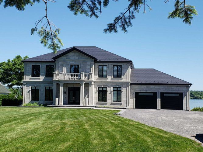 exterior of large grey home with new roof and big front lawn