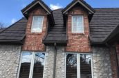 charcoal shingles on roof of home with four windows